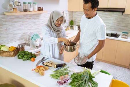 husband help his wife in the kitchen. muslim asian couple preparing dinner together. romantic young man and woman have fun making food at home