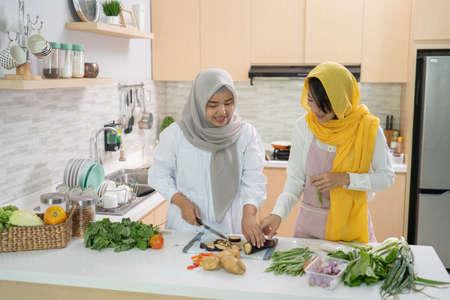 两个迷人的年轻穆斯林女人一起准备开斋晚餐。斋月和开斋节穆巴拉克在厨房做饭