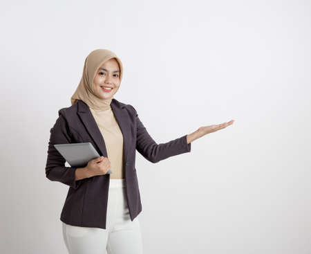 woman entrepreneur wearing hijab smiling with holding tablet showing copy space, formal work concept solated white background