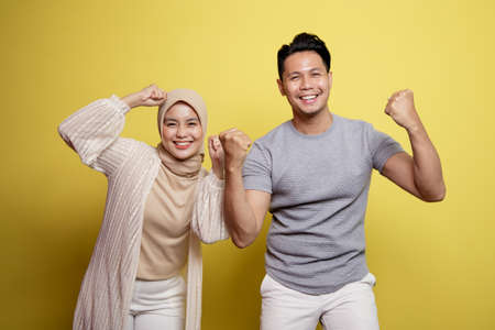 hijab women and men smiling very exciting expression isolated on a yellow background