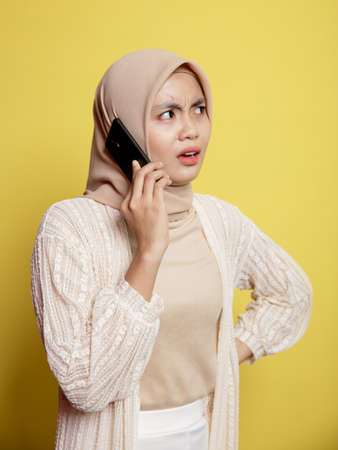 woman hijab with a calling phone expression isolated on yellow background