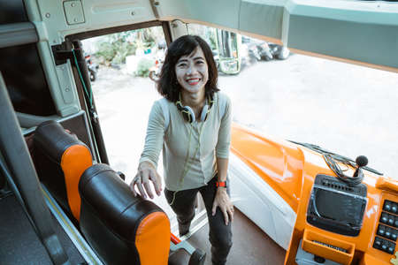 a woman wearing headphones smiles through the bus door as she gets into the bus