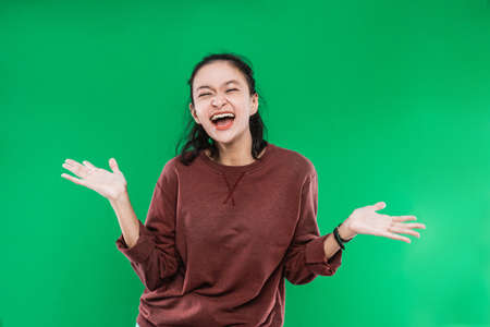 young Asian woman expressing happy wide-open mouth looking to the camera while causing the palms to rise open on green background