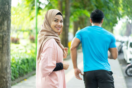 a girl in a veil smile looking at the camera when doing jogging together when outdoor exercise in the park