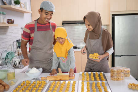 happy muslim family with hijab making nastar cake together at home. beautiful parent and child cooking activity for eid mubarak