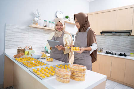 beautiful young muslim woman holding tablet pc while baking a nastar cake at home