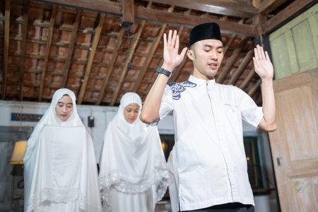 Asian muslim family praying jamaah together at home. Stock Photo