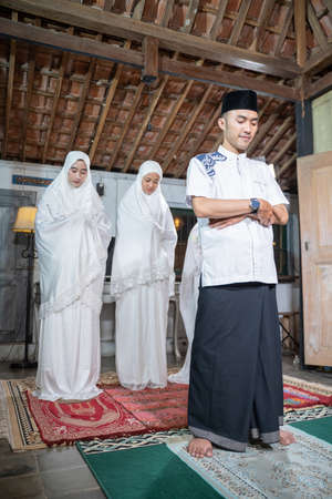 Asian muslim family praying jamaah together at home.
