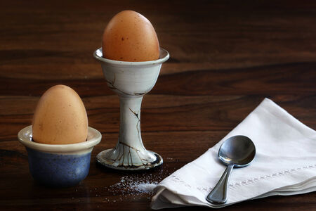 egg cups: Breakfast, two eggs in egg cups, spoon and napkin on a dark brown table Stock Photo