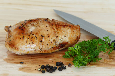poultry meat, roast turkey steak on wooden board with knife, herbs and pepper photo
