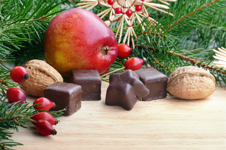 goodies: Christmas goodies in Christmas decoration, red apple, chocolate, walnut,   fir branches and rose hips, copy space