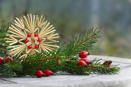 uncluttered: christmas decoration, straw star, rose hips and pine branch, uncluttered arangement outside, copy space
