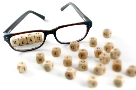 glasses and read message written in wooden blocks, isolated on white background, some blurry letters around, symbol, concept photo