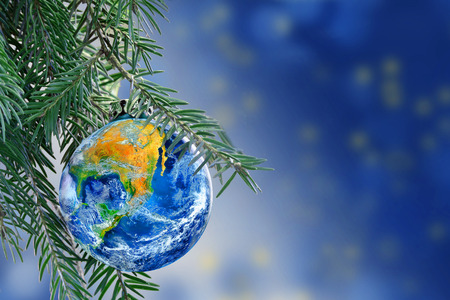 earth globe as a Christmas bauble on fir branch of a christmas tree, Merry Christmas all over the world, copy space.  Archivio Fotografico