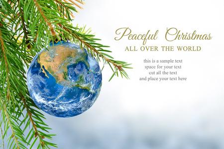 symbol peace: globo de la tierra como bola de Navidad colgando de la rama de abeto, mensaje: Navidad pac�fica en todo el mundo, s�mbolo, met�fora, copia espacio, fondo cubierto de nieve brillante.