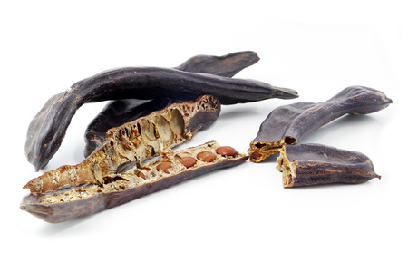 Gruppe von getrockneten Johannisbrotschoten oder Johannisbrot, ganze und halbe mit Samen, isoliert auf weißem Hintergrund Lizenzfreie Bilder