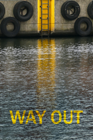 way out: message way out in a deep canal with dark water, and ladder leading upward, can be used for drug problems or diseases such as depression Stock Photo