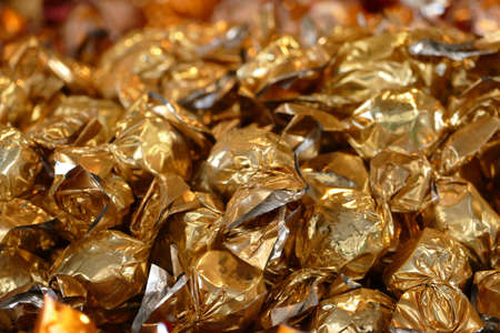 candies wrapped in golden metal foil, glittering background for christmas, new year or easter photo