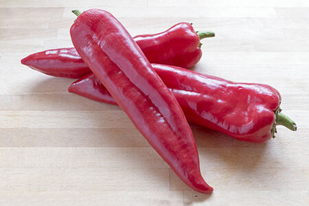 pointy: three red sweet pointy peppers (capsicum) on a wooden board