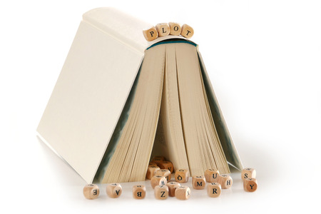 creativ: plot - message spelled out in wooden letters on top of a book that is set up like a house, several letters at the bottom, metaphor for story and creativ writing, isolated on a white background Stock Photo