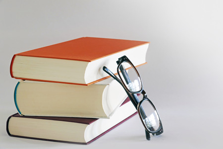 stack of three books with reading glasses leaning against the side, gray background, copy space photo