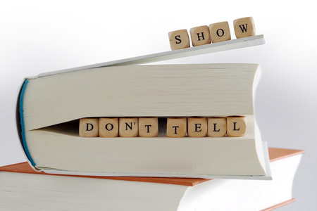 creativ: message - show do not tell - for creativ writing, spelled with wooden letter blocks on the top and between pages of a  book