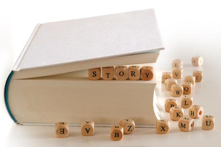 Geschichte - Nachricht für creativ schriftlich mit hölzernen Brief Blöcke zwischen den Seiten eines weißen Buch mehrere verschwommene Buchstaben Blöcke um Dinkel