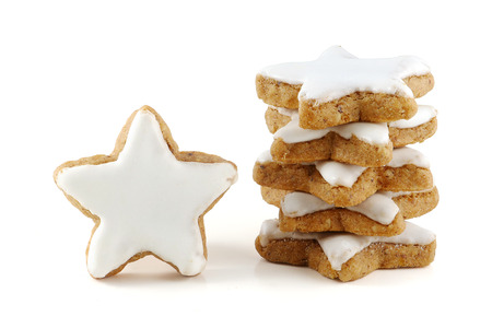 Weihnachtsplätzchen, Stapel von Zimtsterne, einen einzigen stehend, in Deutschland genannt Zimtsterne, close up isolatet auf weißem Hintergrund