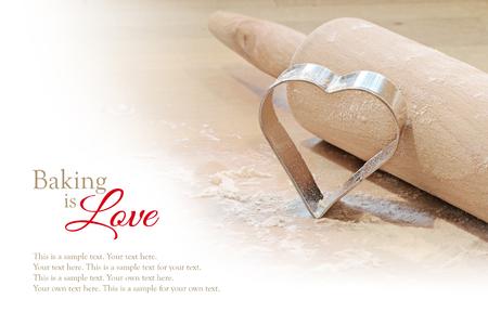 Backen ist Liebe, Hintergrund mit Nudelholz und Cookie-Cutter in Herzform, weiße, Beispieltext unscharf
