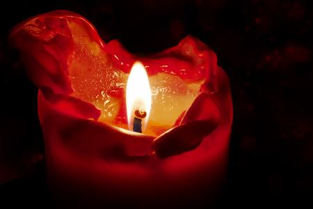 rote Kerze mit Flamme und schmelzendes Wachs vor einem dunklen Hintergrund mit Bokeh, kann für Weihnachten, Geburtstag, advent oder neue Jahr genutzt werden, sondern auch für Trauer, Tod und Hoffnung