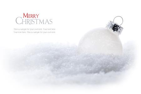helle Weihnachtskugel im Schnee isoliert auf weißem Hintergrund, Beispieltext in dem Kopie-Raum Lizenzfreie Bilder
