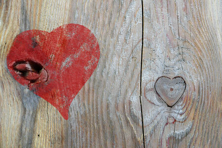 red heart paintet on weathered gray wood with knothole in heart shape, love background, copy space Stock Photo