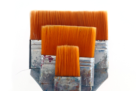flat brushes: three flat brushes with orange bristles and dirty gray handles, isolated on white background