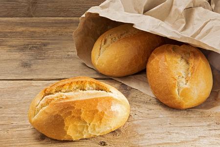 Brötchen in einer Papiertüte auf einem rustikalen Holztisch, frisch aus der Bäckerei zum Frühstück