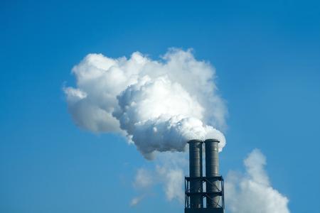 Kamin mit industriellen Rauch gegen den blauen Himmel