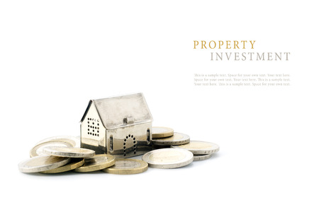 property investment, silver golden house model on coins isolated on white background, copyspace with sample text