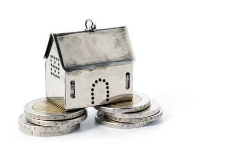 real estate investment: real estate investment on reliable foundation, small silver model house stands on two strong stacks of coins, concept immage, isolated on white background with copy space Stock Photo