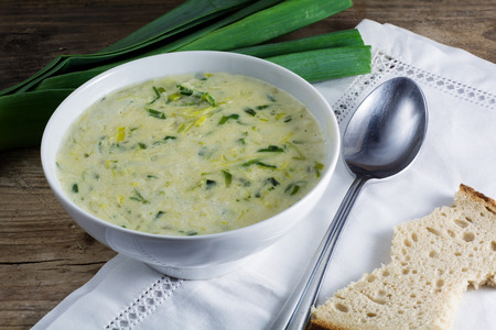 leek cream soup in a white bowl with spoon, napkin and fresh leek od rustic wood Stock Photo