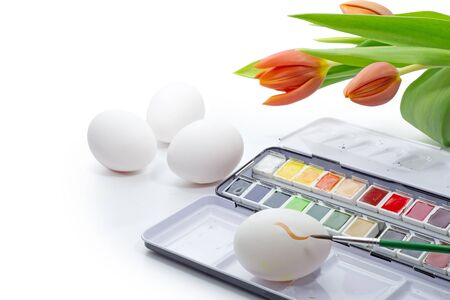 coloring easter egg: coloring Easter egg, watercolor box, white eggs, brush and tulips isolated on white as a corner background with copy space Stock Photo