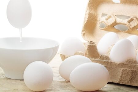 blow out: blow out eggs to paint for Easter decoration, white egg over a bowl and eggs in the carton