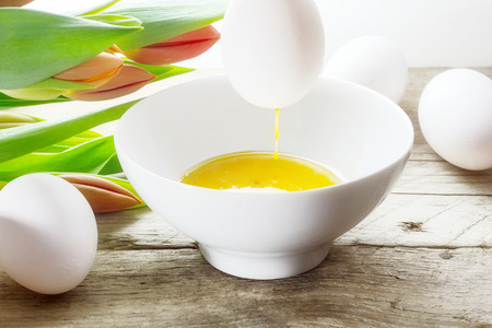 blow out: blow out eggs for Easter decoration, egg with dreop of rinning yolk over a bowl, more white eggs and tulips in the background
