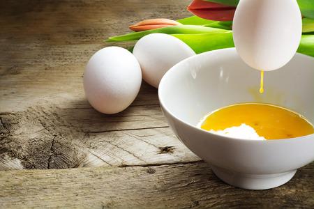 blow out: spegnere le uova per la decorazione di Pasqua, uovo con Rinning tuorlo sopra una ciotola, le uova pi� bianche e tulipani in background su legno vecchio, copia spazio