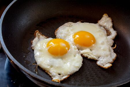 white eggs: two fried eggs in a black pan, breakfast preparation Stock Photo