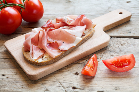 hearty: hearty bread with ham  bacon and some tomatoes on a wooden board for a rustic supper