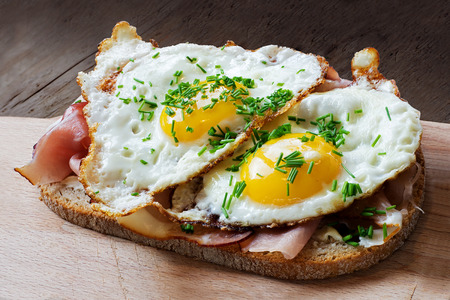 egg white: slice of rustic bread with ham or bacon and fried egg, typical  in germany called strammer max Stock Photo