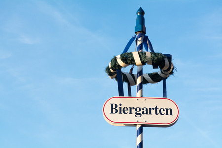 divert: wreath and shield with the german word Biergarten on a blue and white pole, this sign is pointing to a Bavarian beer garden, blue sky in the background with copy space