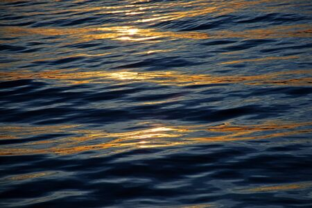 liquid gold: stripes of sunset reflections like liquid gold on the calm sea waves, vacation background