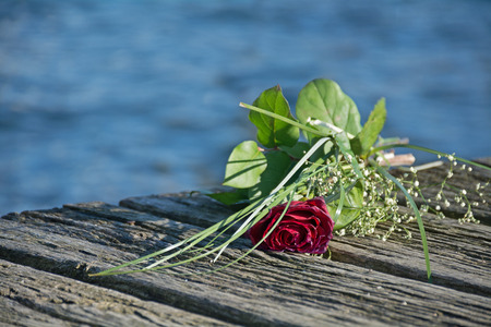 last love greeting, rose bouquet on the old wooden pier during a burial at sea, copy space