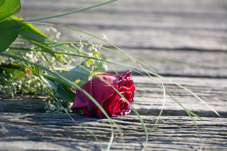 fade away: thrown away love, rose bouquet forgotten and withered on the old boardwalk, copyspace