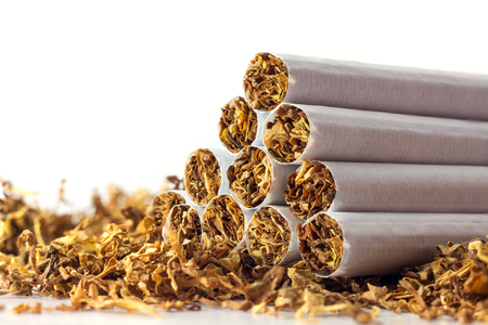 cigarettes in loose tobacco, close up with copy space in the white background Standard-Bild
